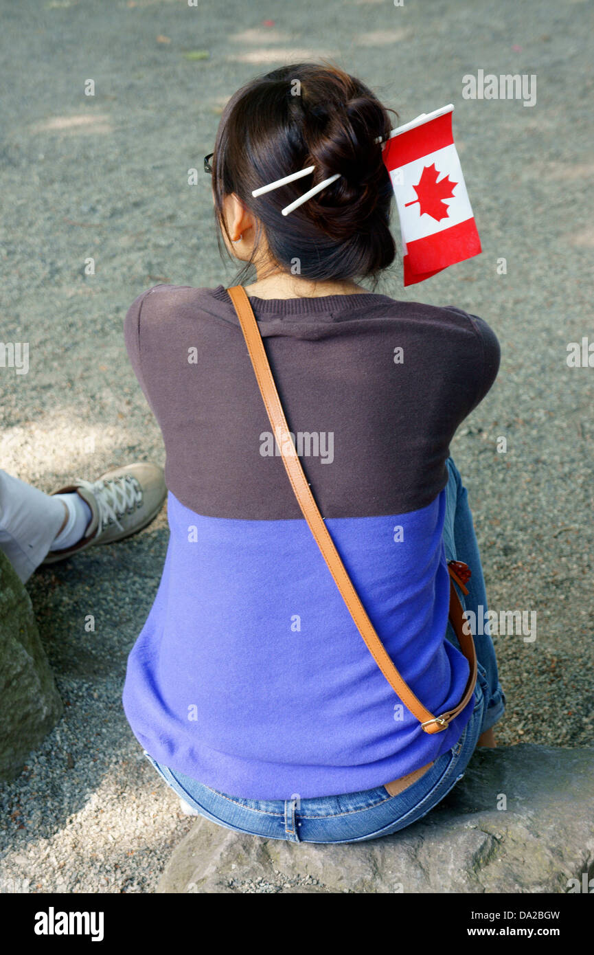 Young woman of Asian descent with Canadian flags in her hair at Canada Day celebrations, Vancouver, British Columbia, - Stock Image