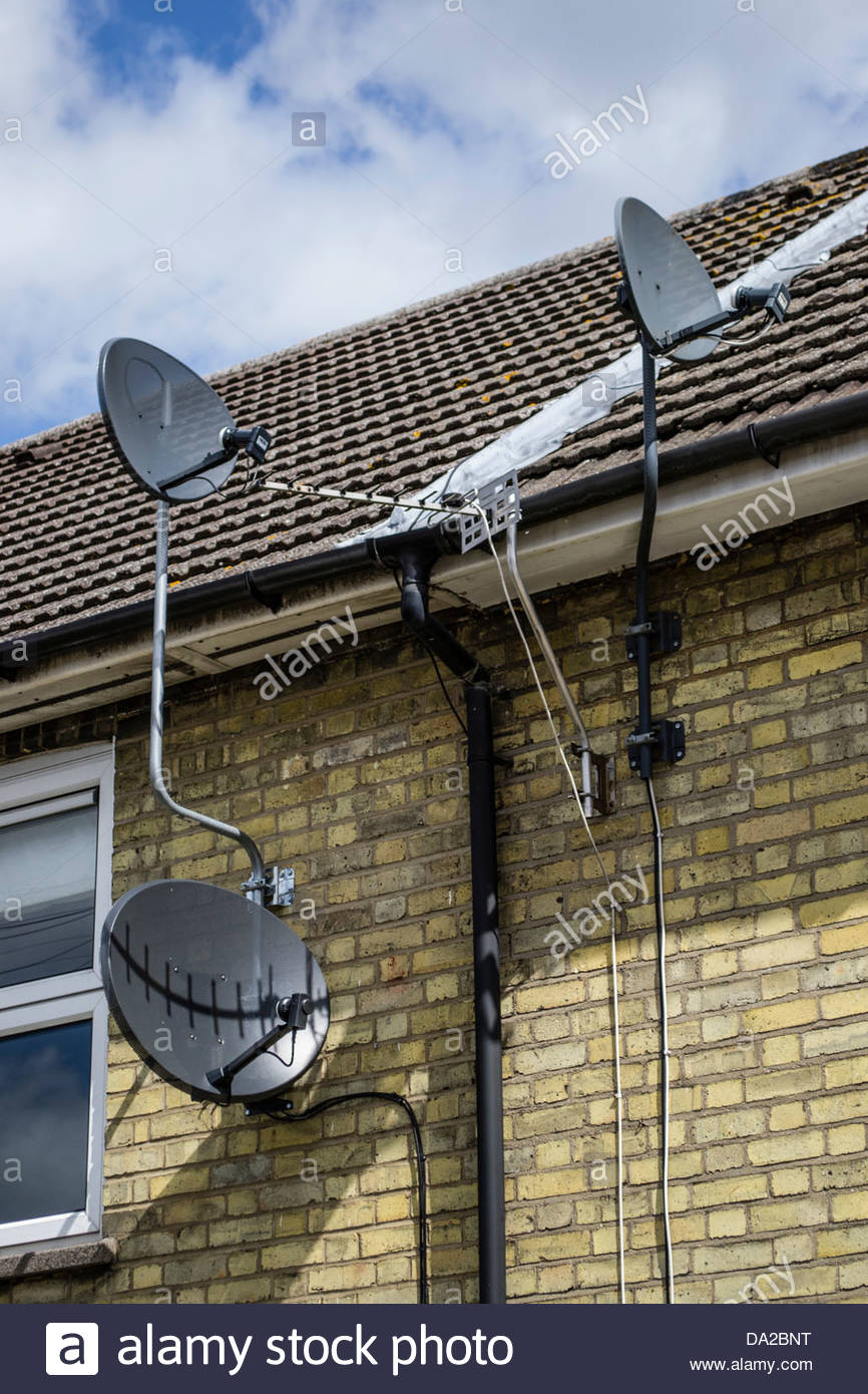 Satellite dishes and TV aerial on a residential house in Cambridge - Stock Image
