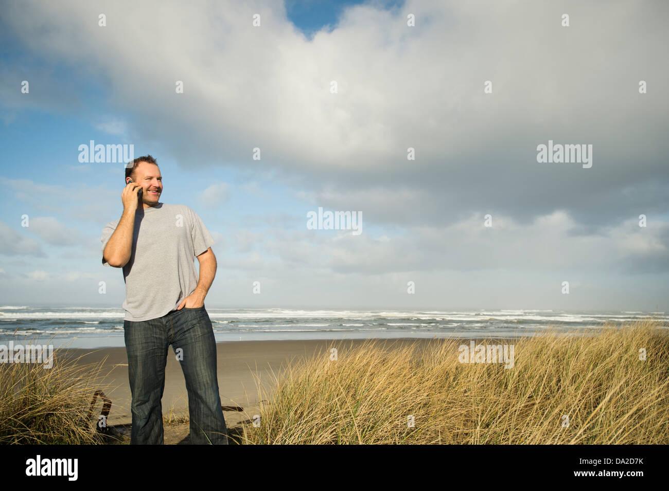 USA, Oregon, Rockaway Beach, Man on phone while standing on beach Stock Photo
