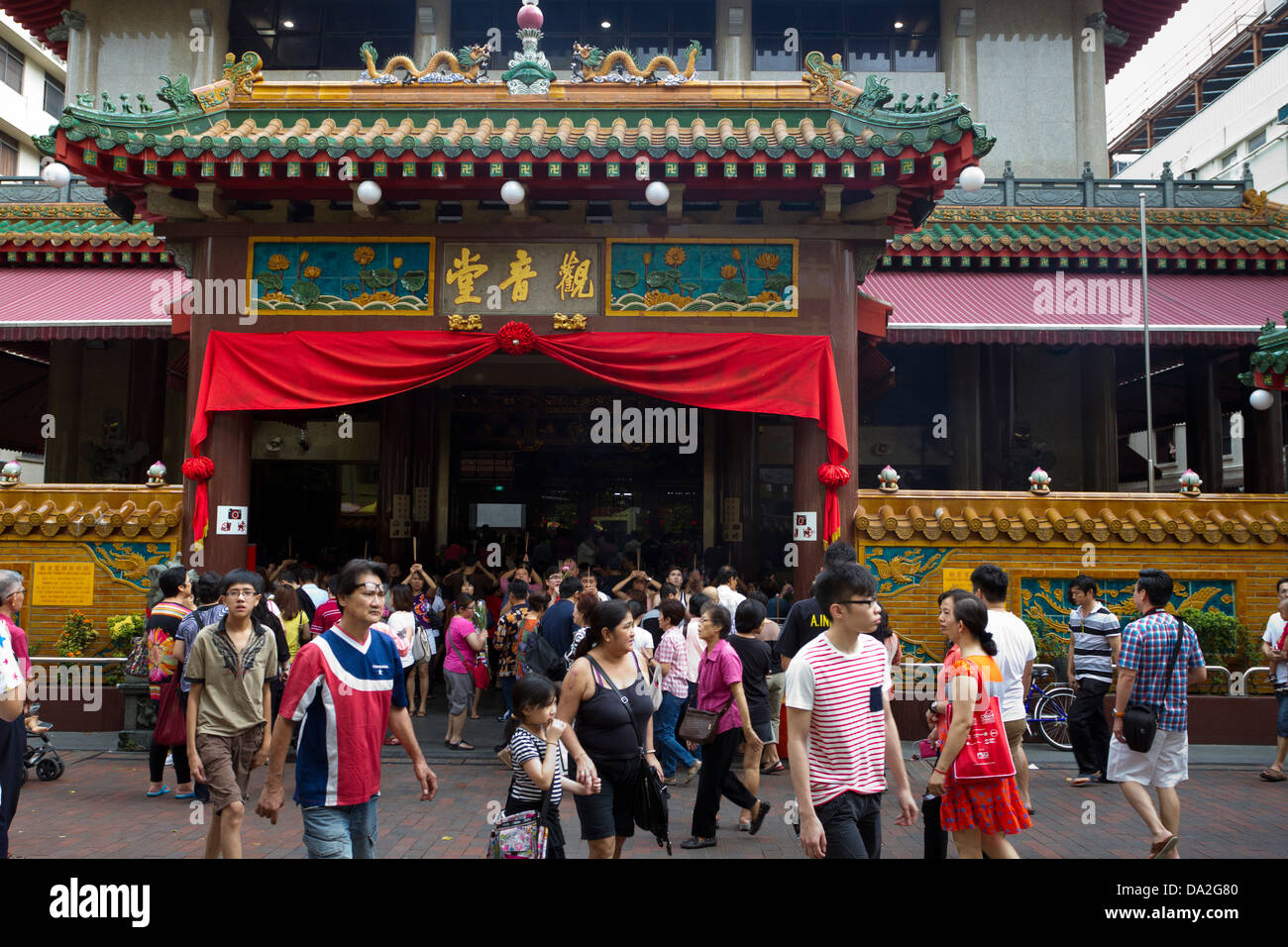 People standing and walking around outside Kwan Im Thong Hood Cho Temple, Bugis, Singapore - Stock Image