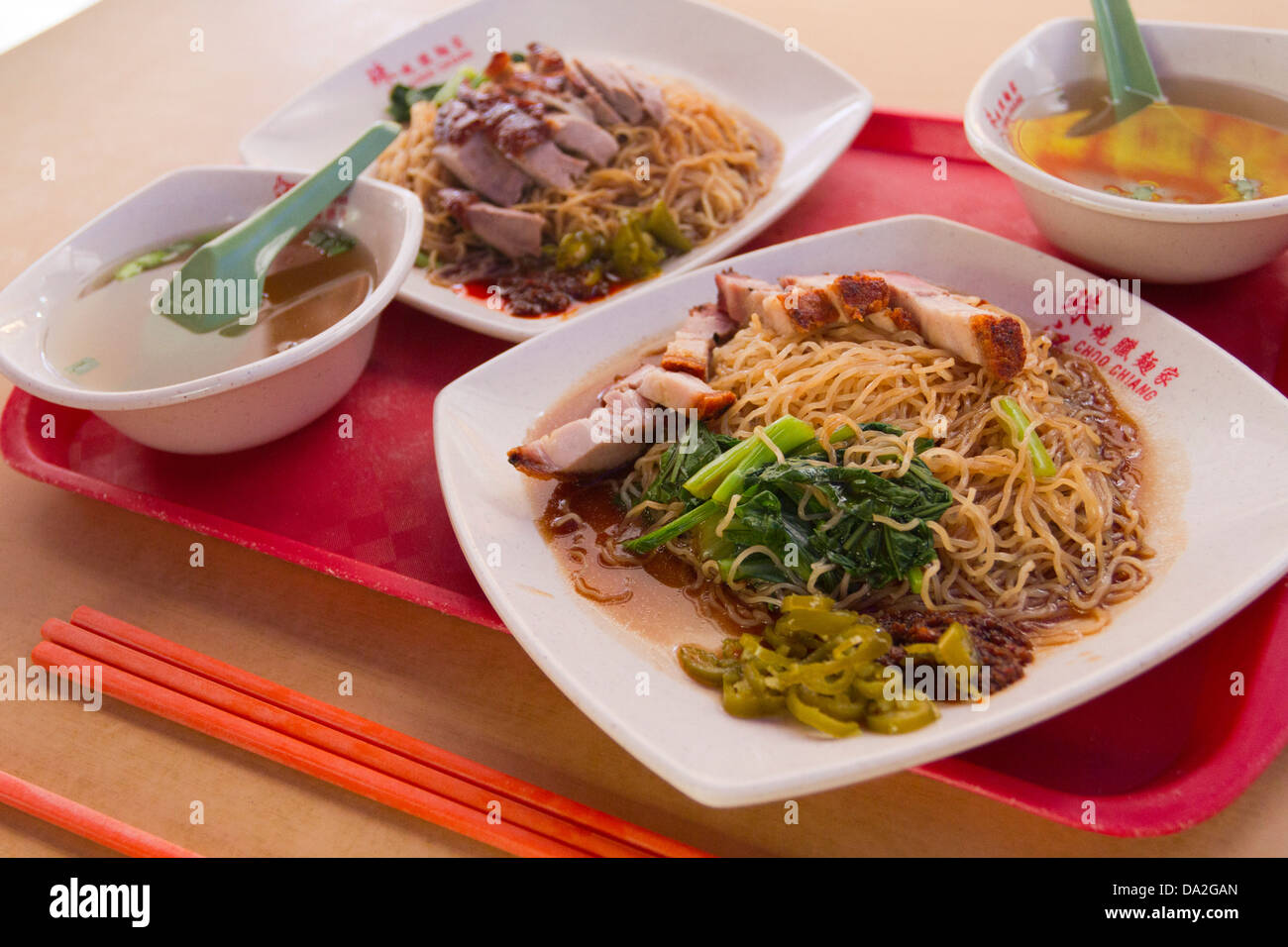 Two plates of Chinese food, one with roast duck and noodles, the other with crispy belly pork, Bugis, Singapore - Stock Image