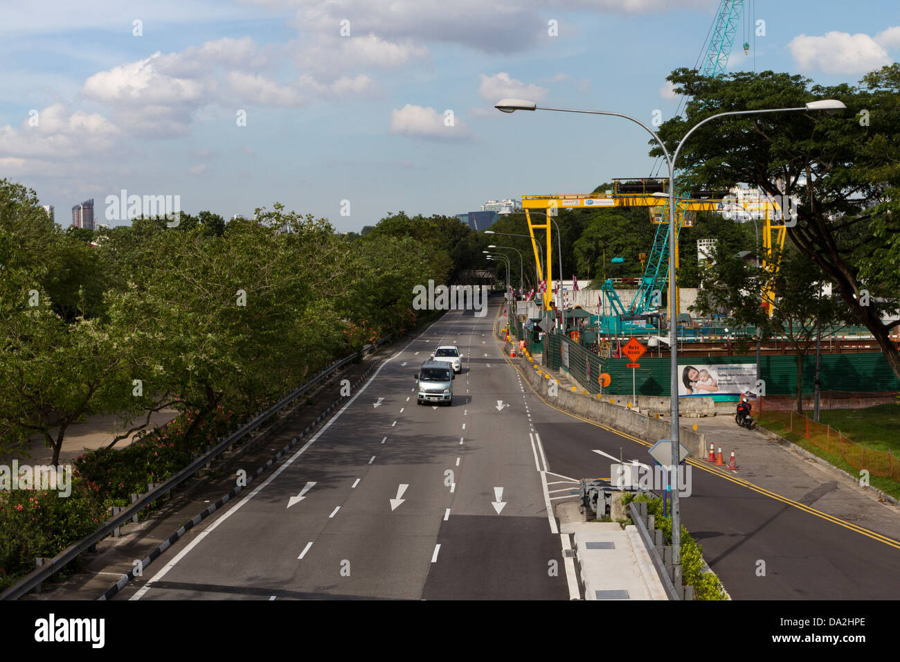 Road with construction machinery next to it, Singapore, Asia - Stock Image