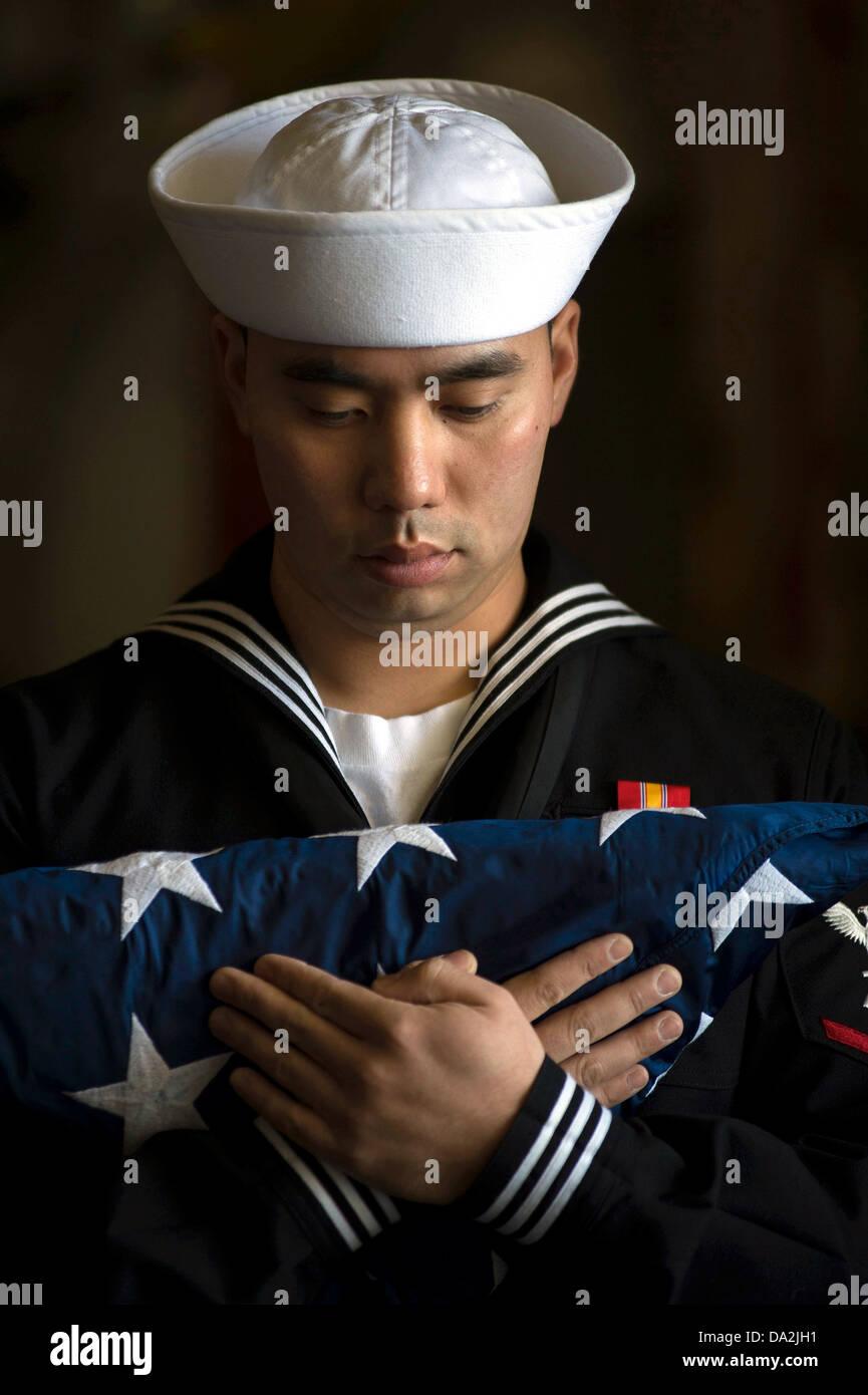 A US Navy sailor bears the flag during a burial at sea aboard San Antonio-class amphibious transport dock ship USS - Stock Image