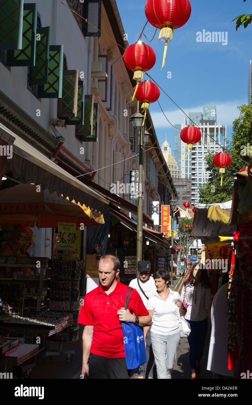 People walking in Chinatown amongst the tourist and souvenir shops with hanging red lanterns, Singapore - Stock Image