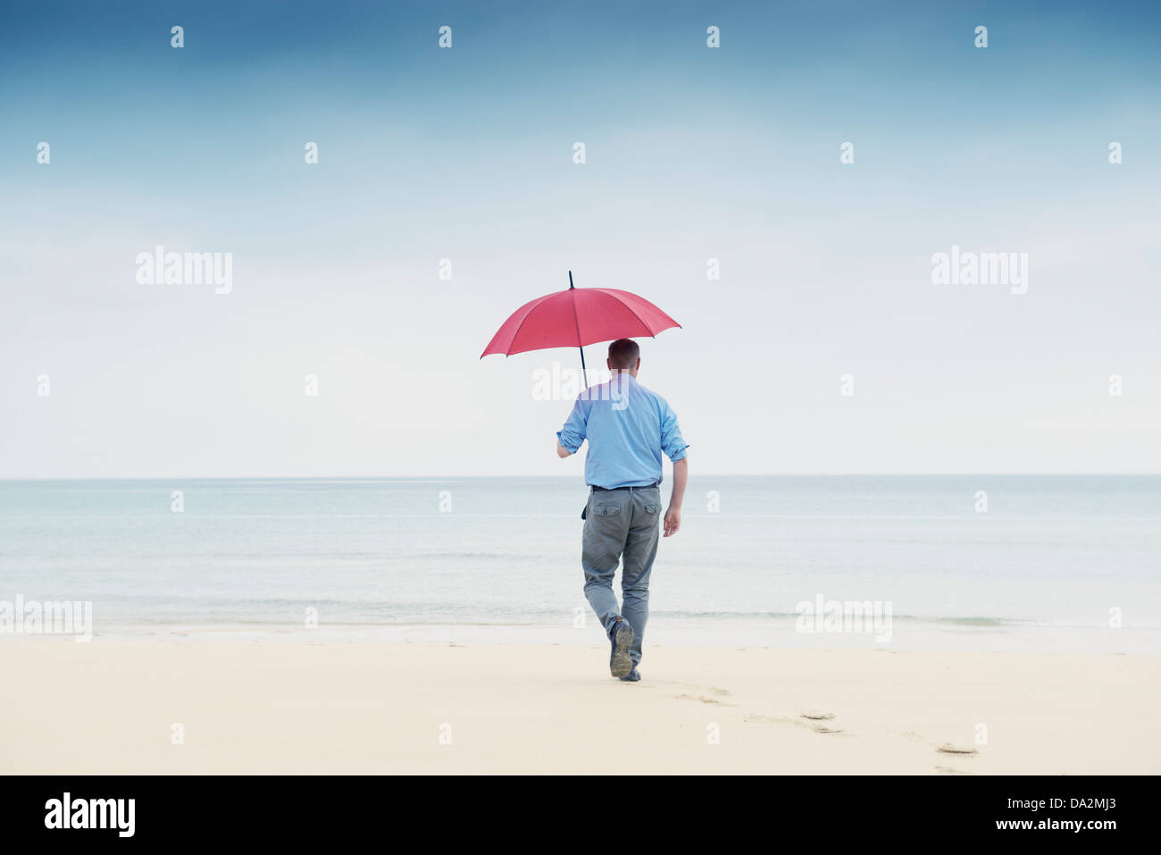 man walks across deserted beach towards calm sea while holding a red umbrella. get away from it all, contemplation, - Stock Image