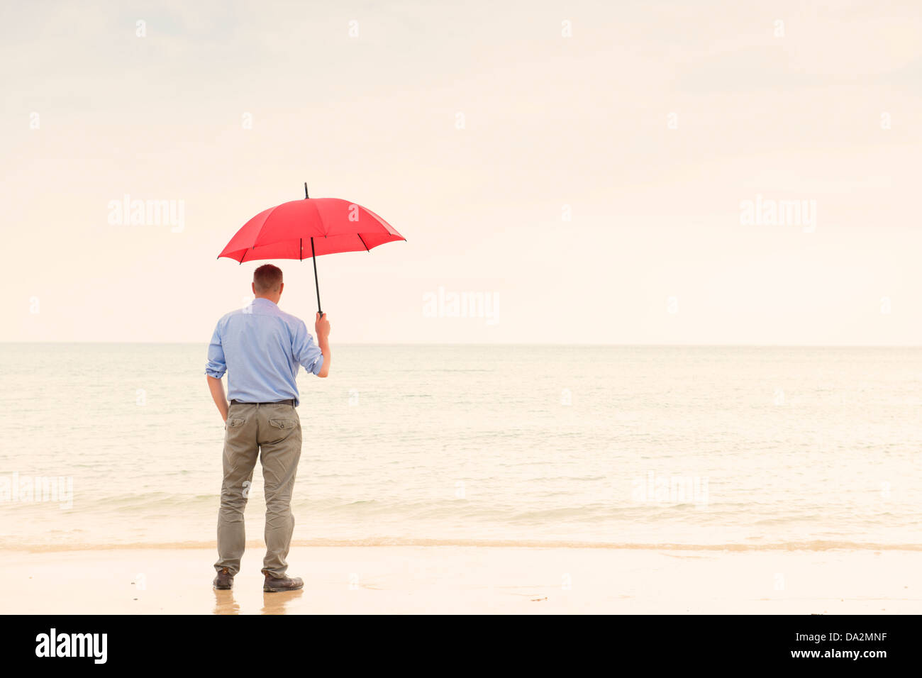 Man stands looking out to sea with red umbrella. Contemplation, solitude, loneliness. - Stock Image