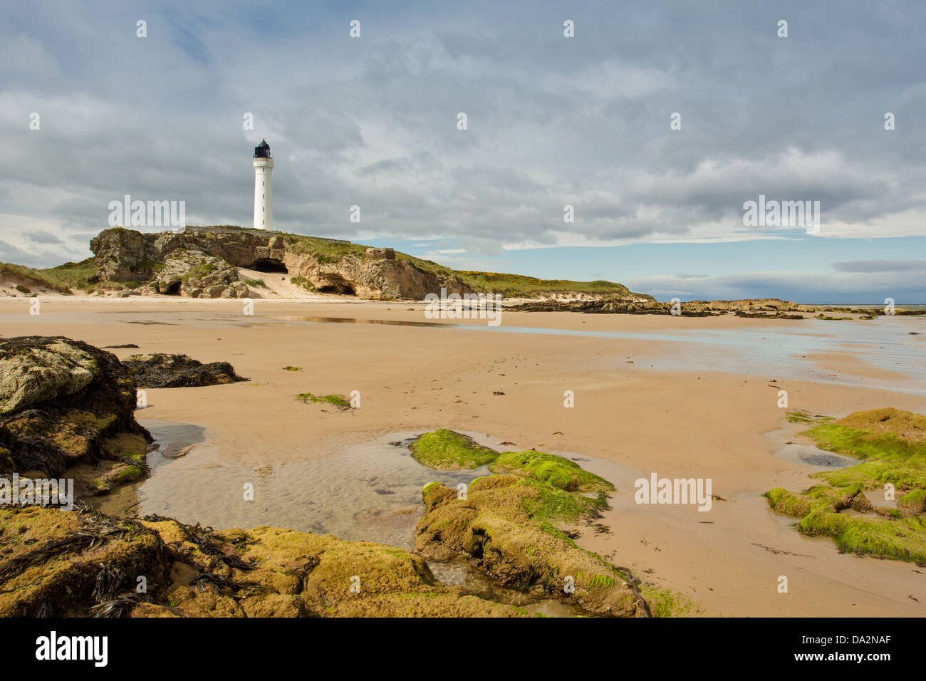 COVESEA SKERRIES LIGHTHOUSE ON THE ROCKS WITH BEACH NEAR LOSSIEMOUTH MORAY SCOTLAND - Stock Image