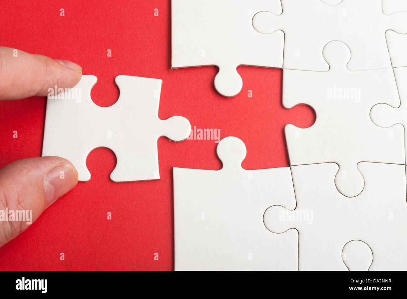 Hand holding puzzle piece and inserting it into group of white paper jigsaw puzzles - Stock Image