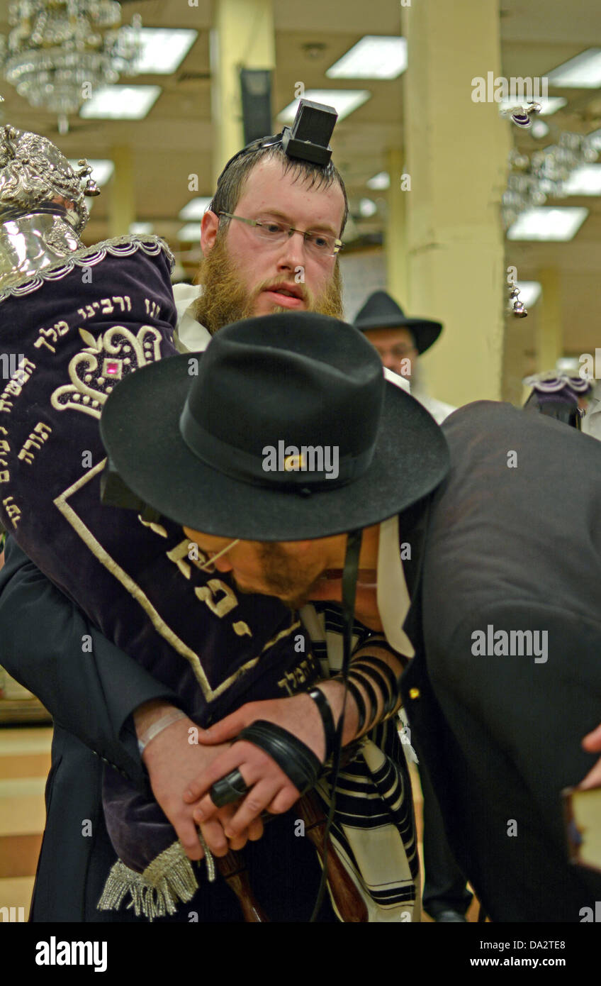 The Torah is kissed by religious Jewish worshipers at morning services at Lubavitch headquarters in Brooklyn, New - Stock Image