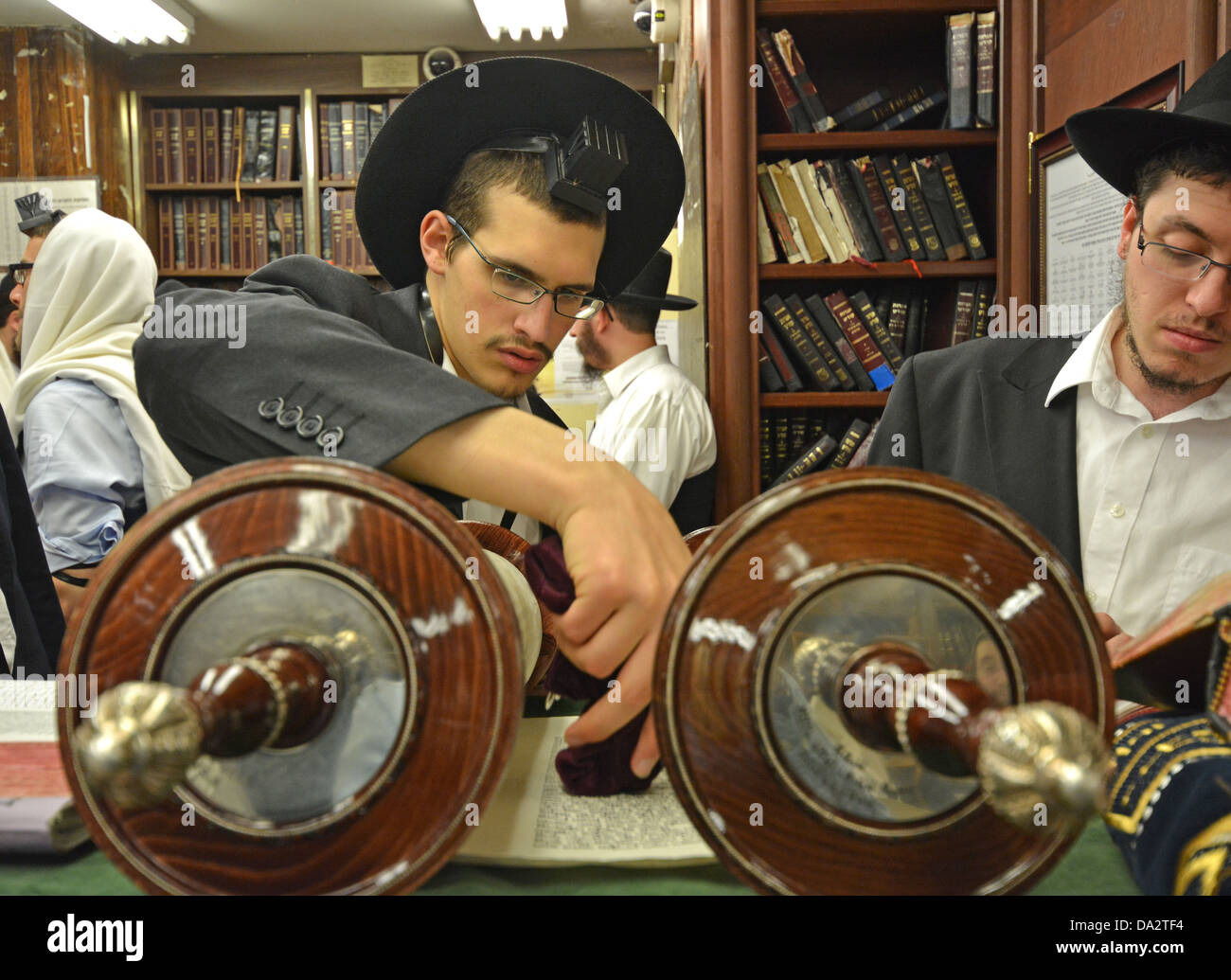 Religious Jewish man blesses the Torah before a reading at weekday services at Lubavitch headquarters in Brooklyn, - Stock Image