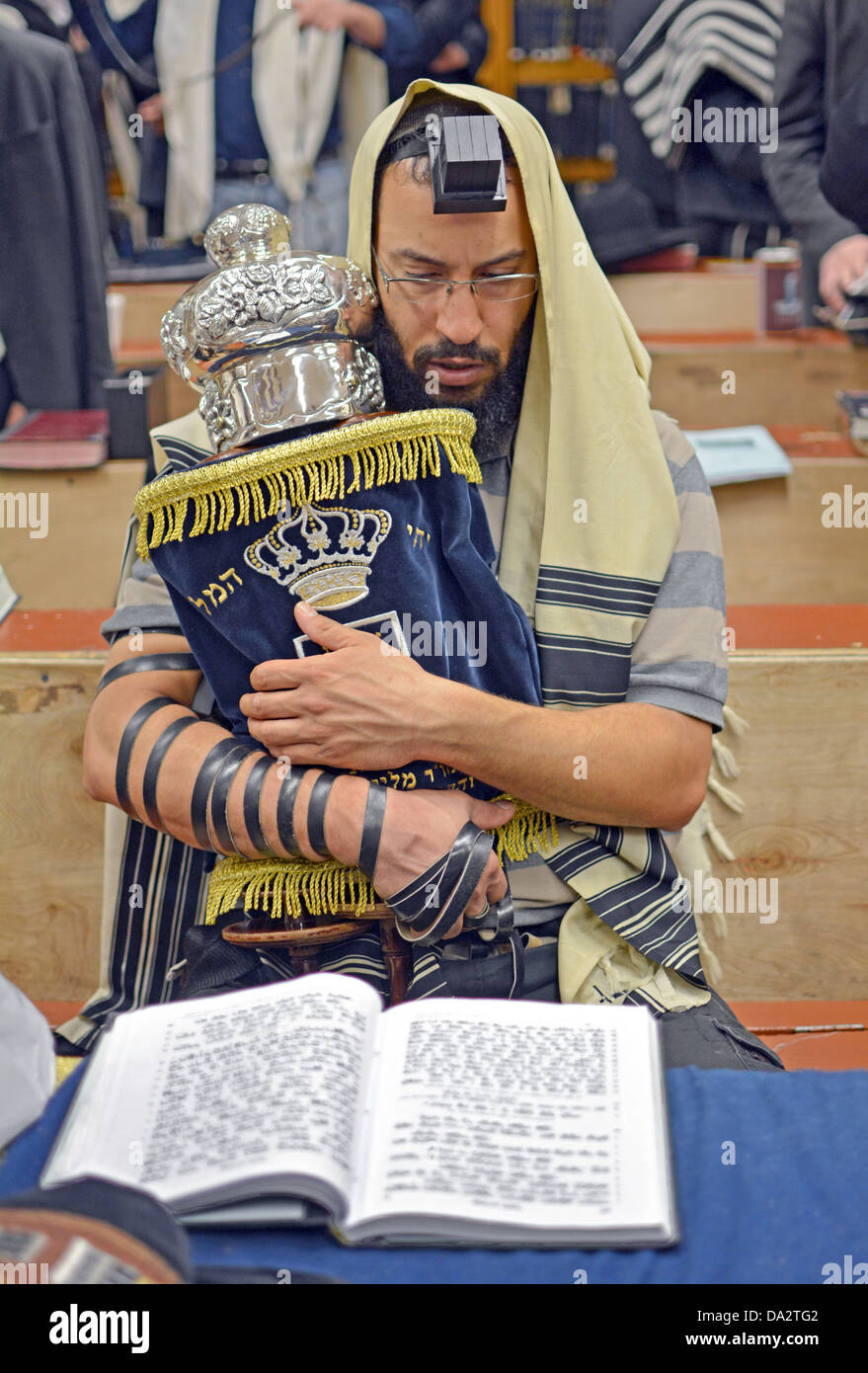 A man wearing a prayer shawl & phylacteries holding a Torah during weekday morning services at Lubavitch  headquarters Stock Photo