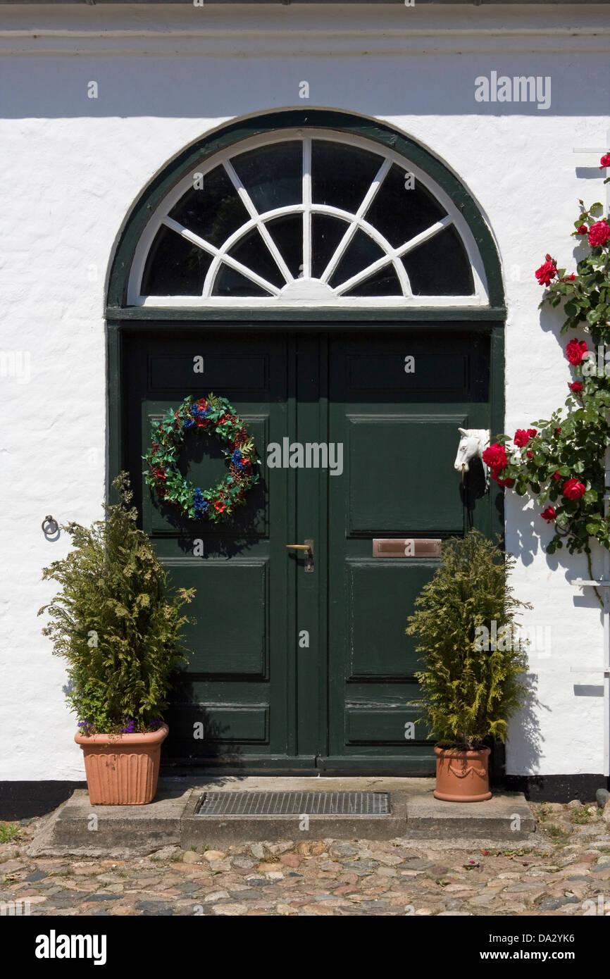 Europe, Germany, Schleswig Holstein, Gluecksburg, Gluecksburg Castle, Gatehouse, historical entrance door with climbing roses Stock Photo