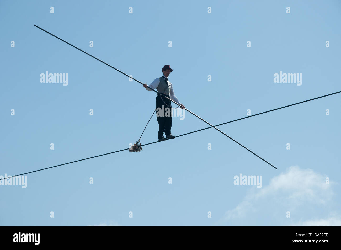 A tightrope walker walks overhead a crowd in the circus area of Glastonbury Festival of Contemporary Performing - Stock Image