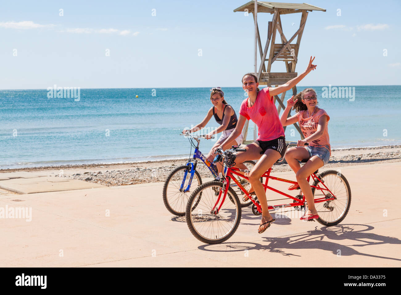 teenage girls riding tandem bicycle by seaside - Stock Image