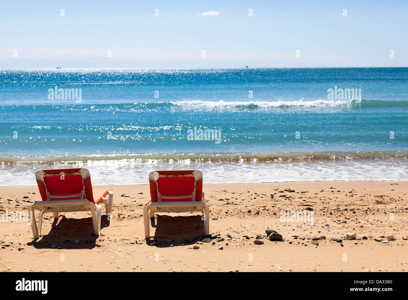 Two empty sun loungers on beach by sea - Stock Image
