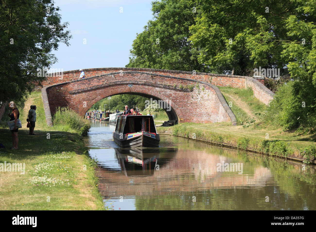 A narrowboat passing under the turnover bridge on the Oxford Canal at Braunston, Northamptonshire - Stock Image
