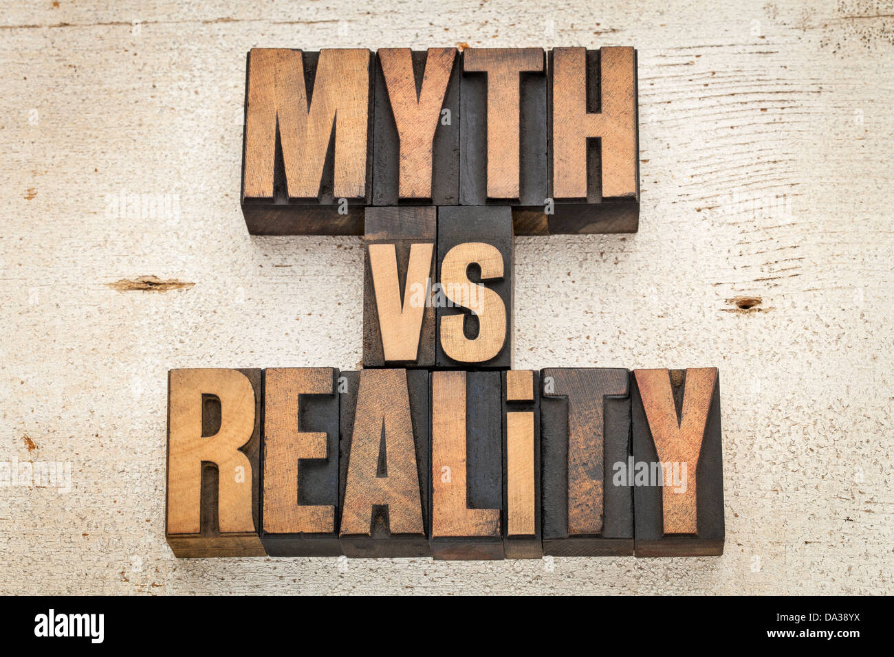 myth versus reality - concept in vintage letterpress wood type on a grunge painted barn wood background - Stock Image