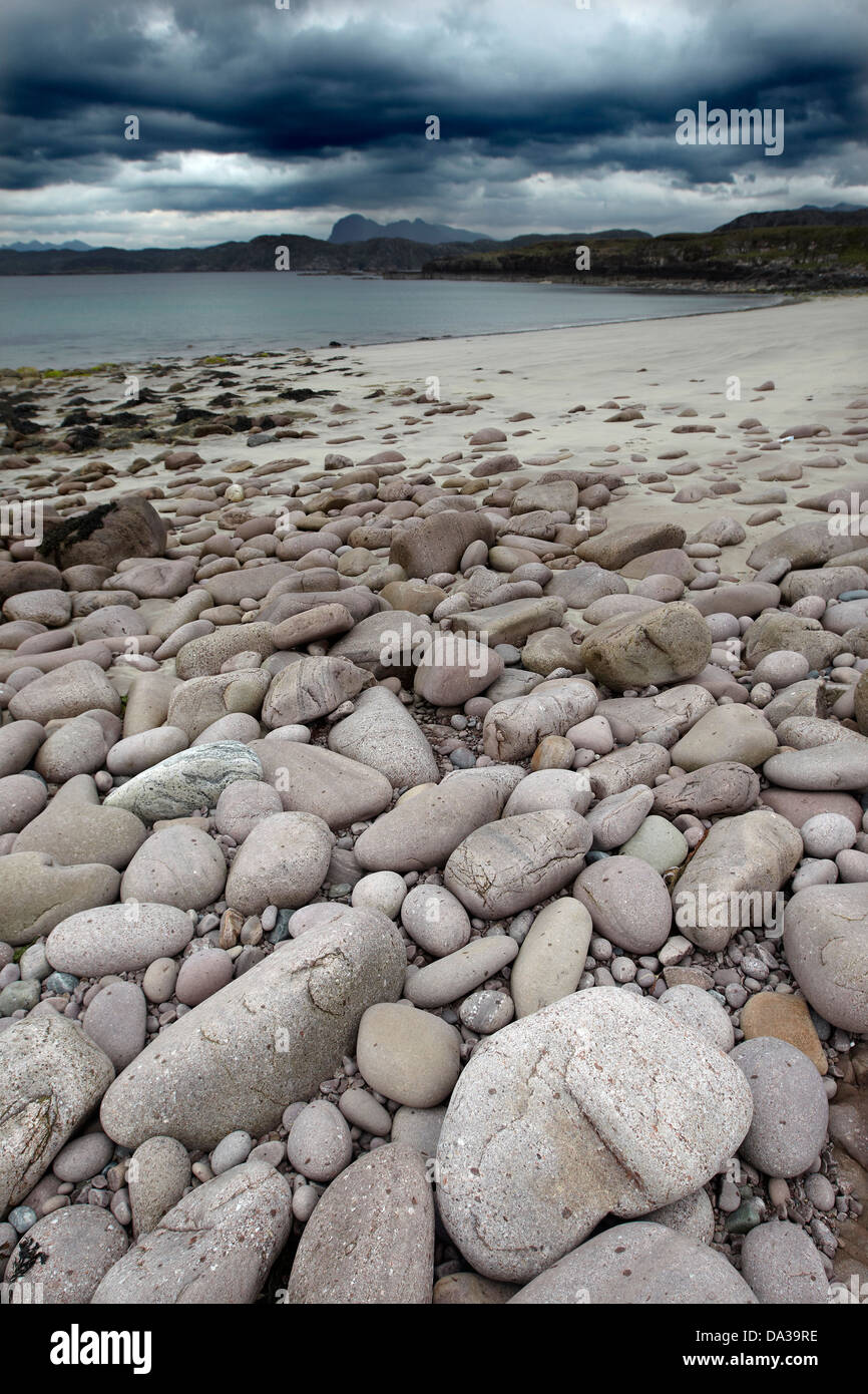 Pebbles on Garvie Beach under a dramatic dark sky, Garvie Bay, Enard Bay, Sutherland, Scotland - Stock Image