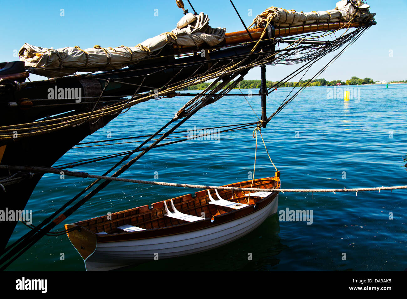 Life boat tied to tall ship in harbor - Stock Image