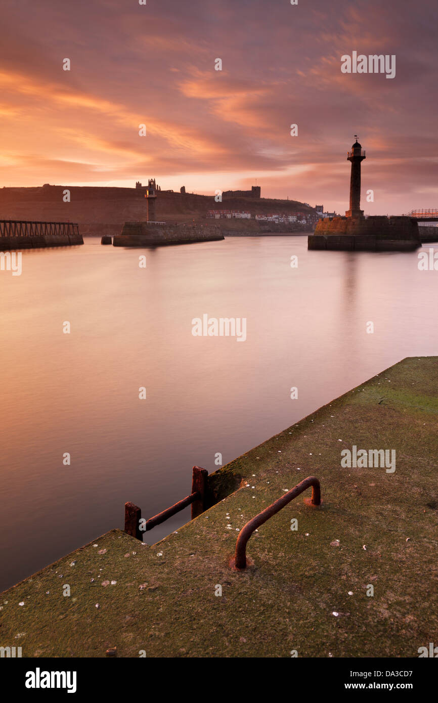 View of the river Esk and Whitby Harbour from the west pier at dawn in winter, with the distant Abbey and St Mary's - Stock Image