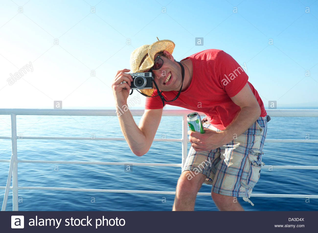 A tall man holding a beer bends over to take a photograph, during a summer ferry crossing in Greece. - Stock Image