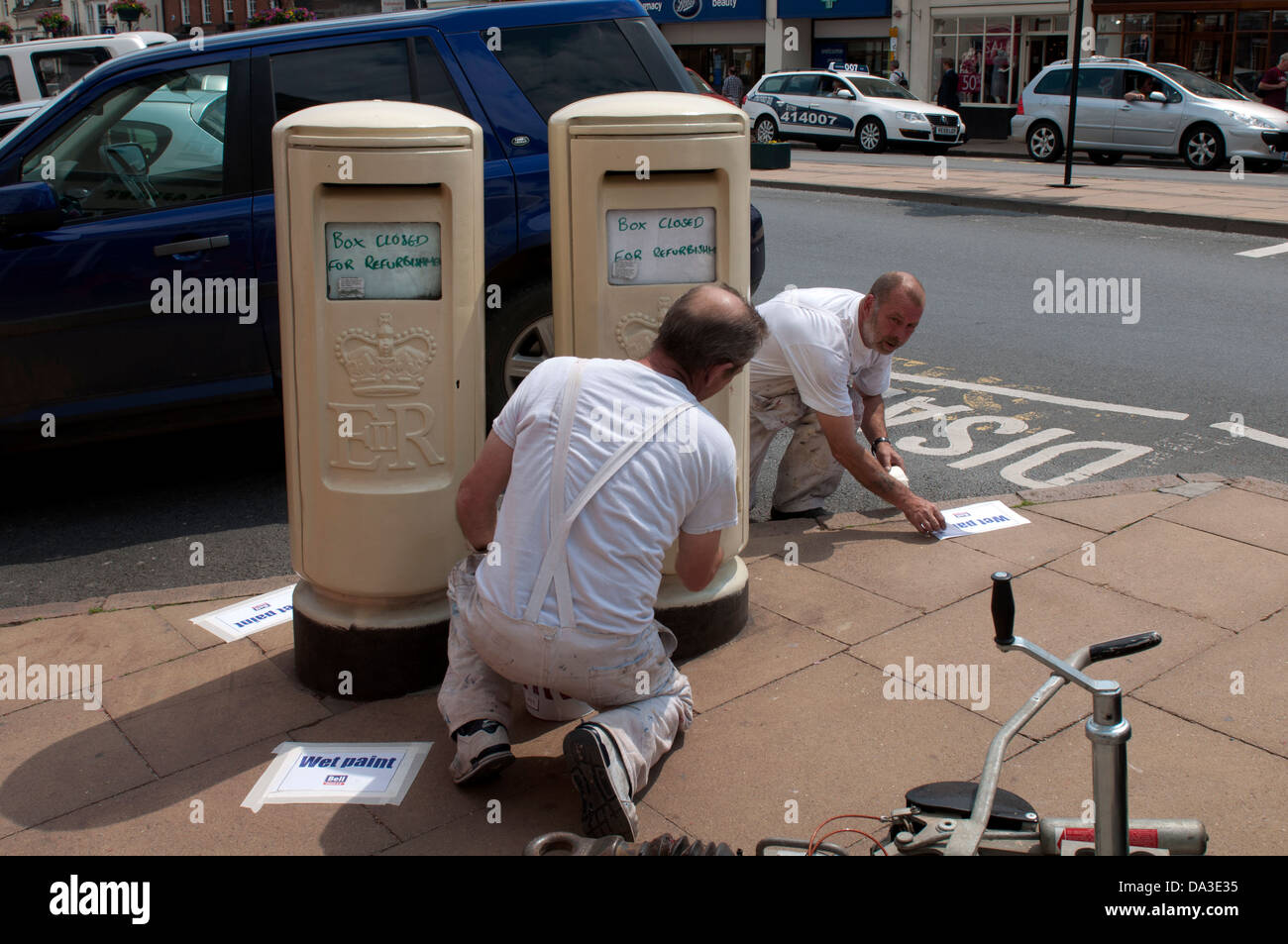 Repainting gold postboxes, Stratford-upon-Avon, UK - Stock Image