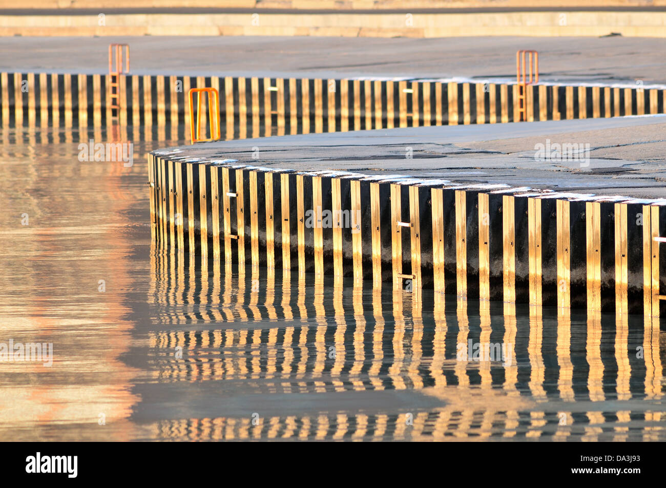 Reinforced lake wall along Chicago's North Avenue Beach area reflection Lake Michigan. Chicago, Illinois, USA. - Stock Image