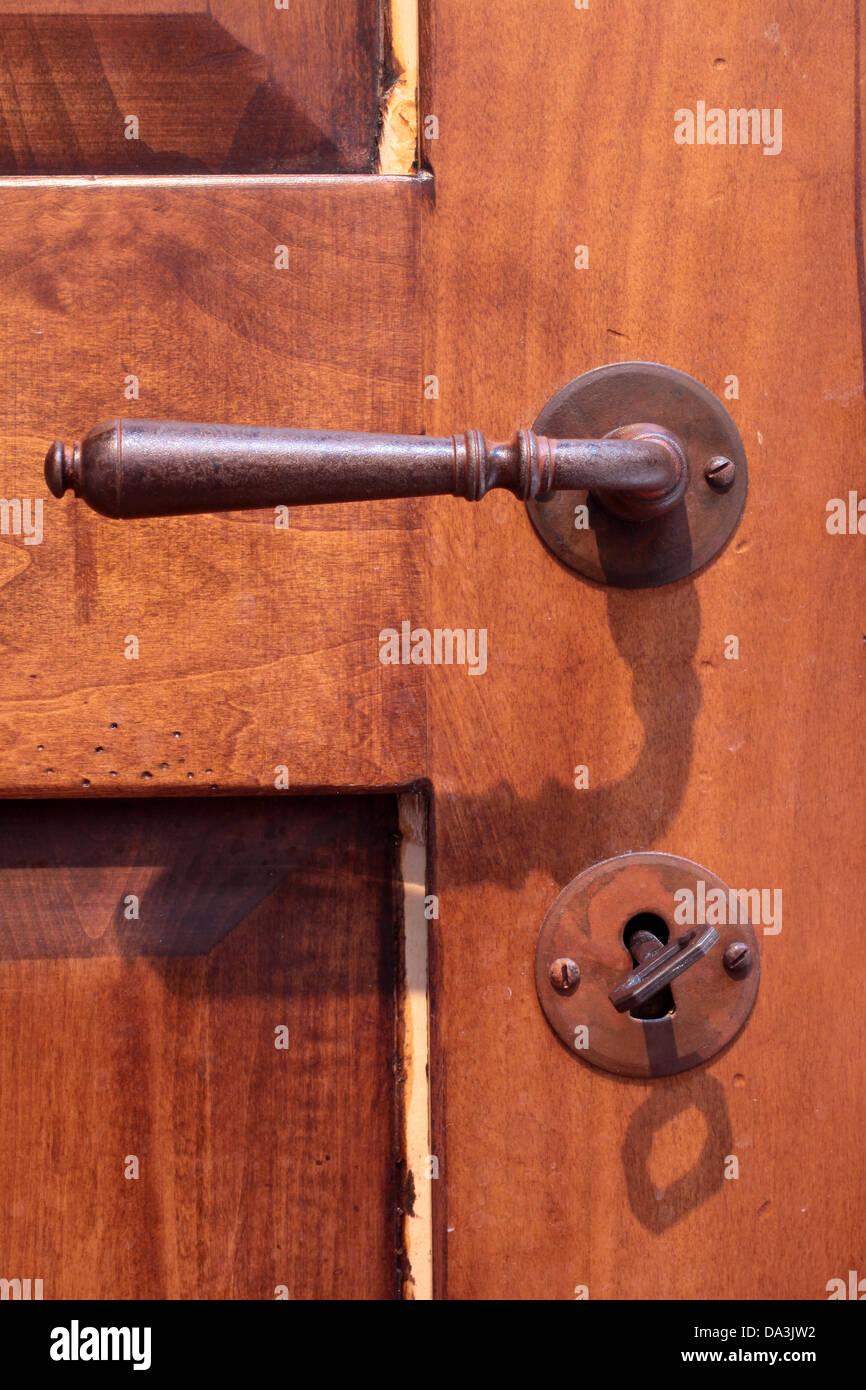 Iron door handle on an old wooden door - Stock Image