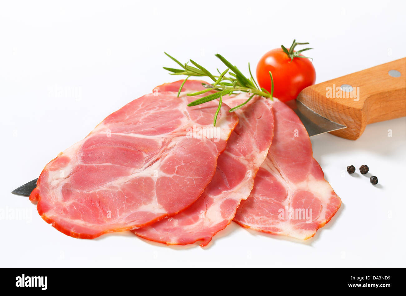 Thin slices of smoked pork on knife Stock Photo