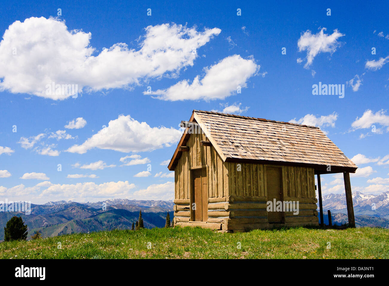 Small rustic log cabin at summit of Bald Mountain in Sun Valley, Idaho, on partly cloudy summer day - Stock Image