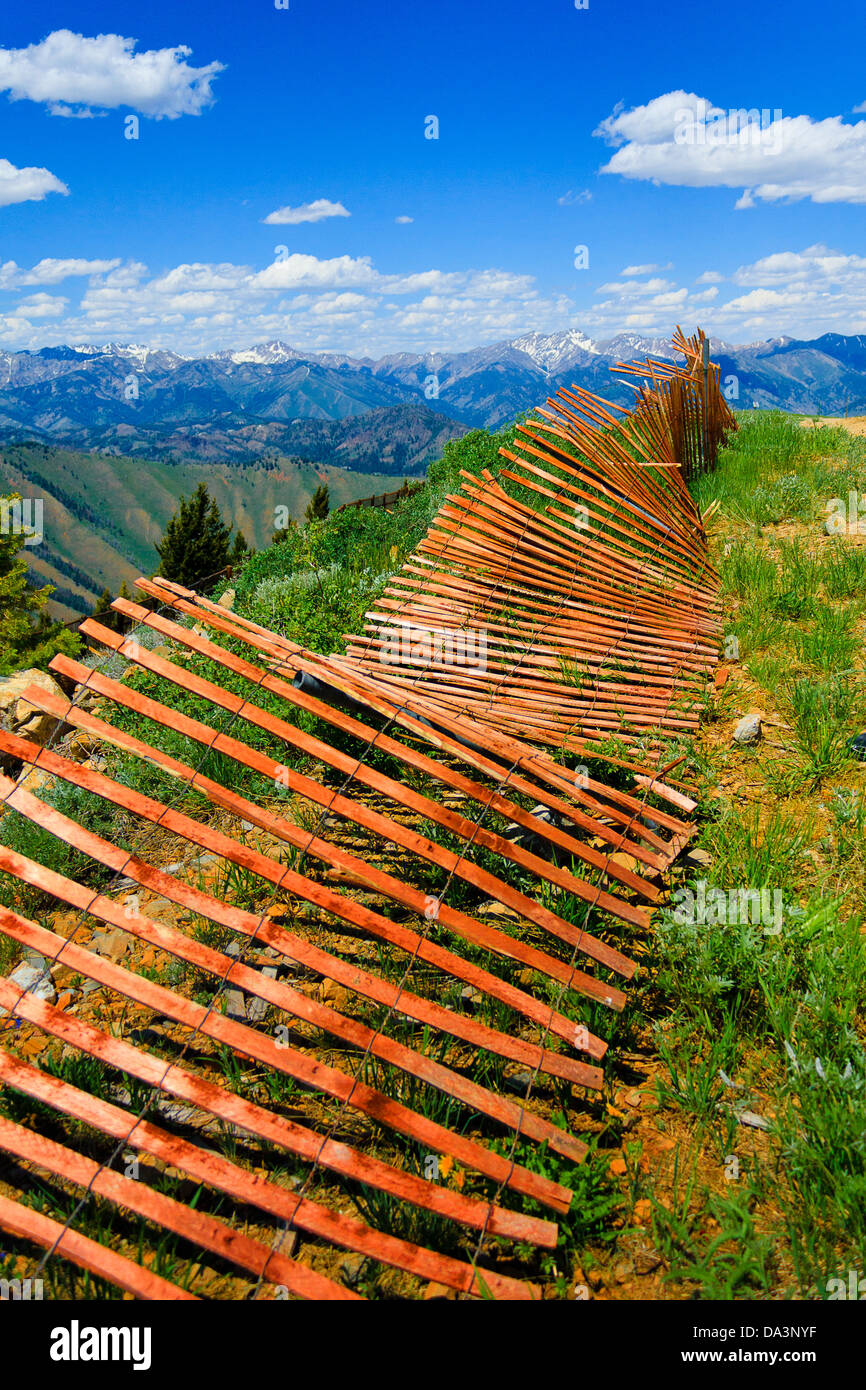 Falling-down orange wooden fence on the summit of Bald Mountain in Sun Valley, Idaho, on partly cloudy summer day - Stock Image