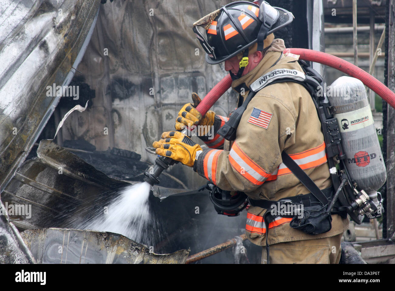 A firefighter using a hoseline to extinguish a hot spot at a fire scene - Stock Image