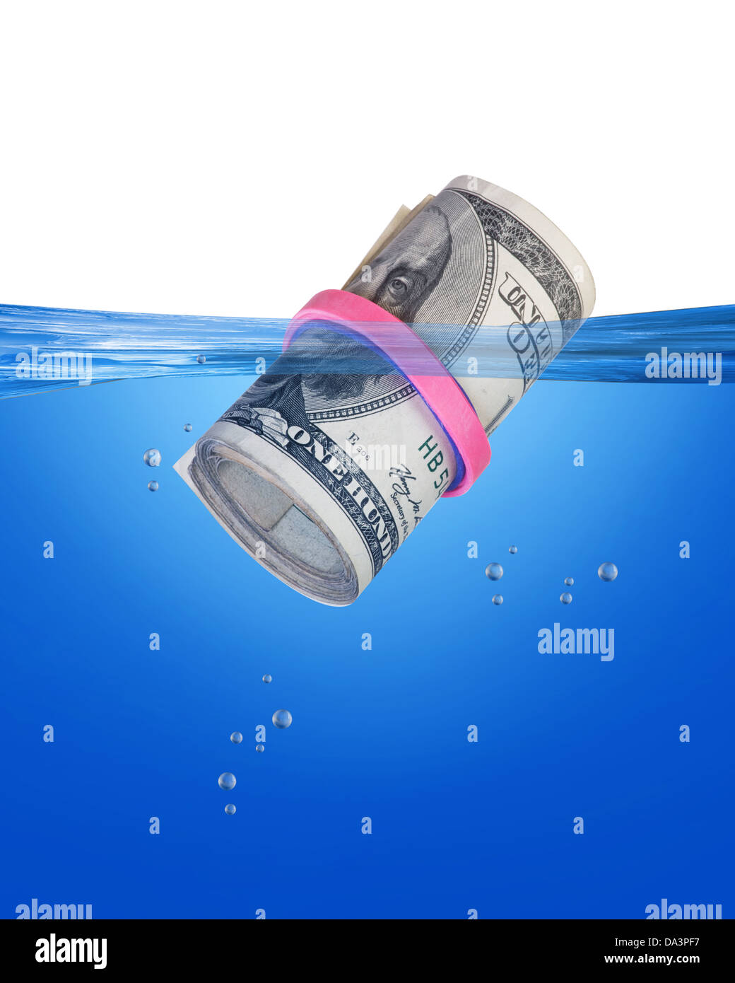 Cash roll floating in blue water. - Stock Image
