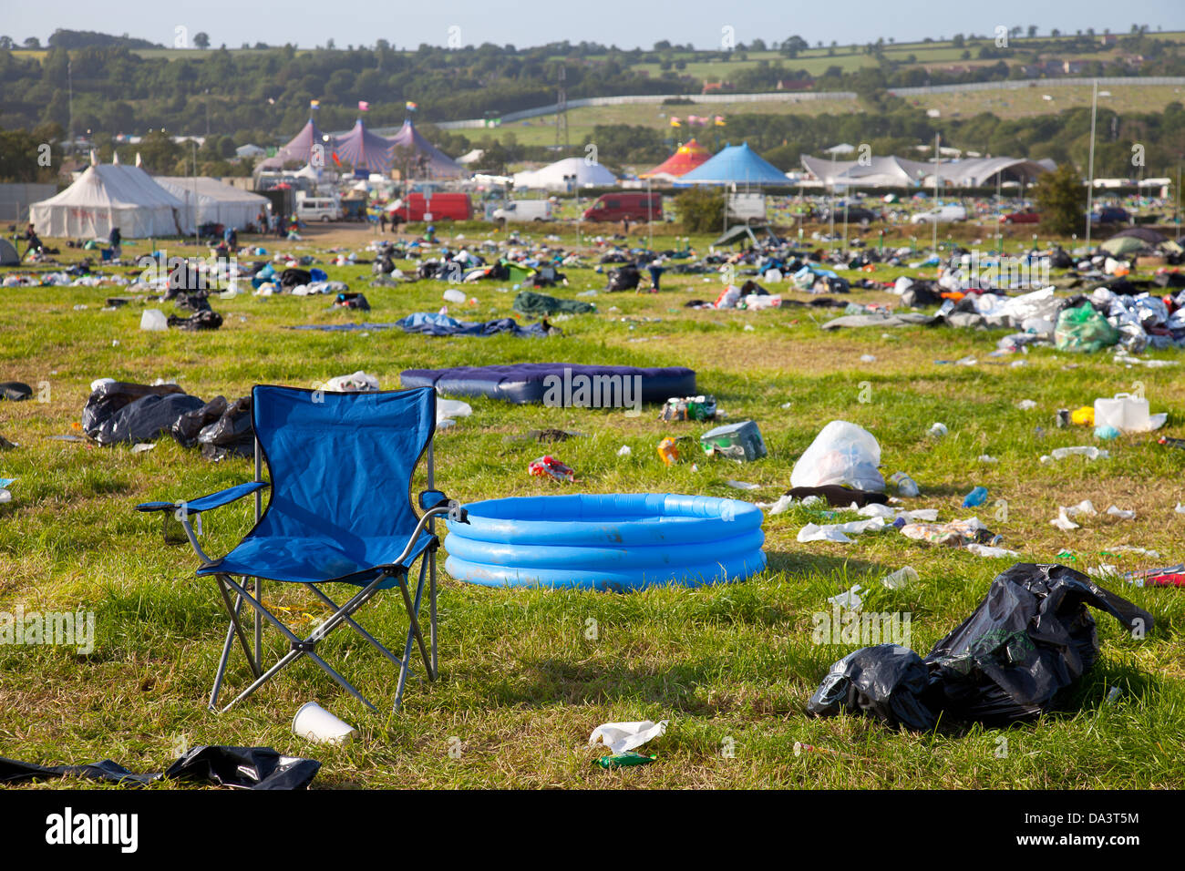 Abandoned tents, paddling pool and chair with rubbish left after Glastonbury Festival 2013 - Stock Image