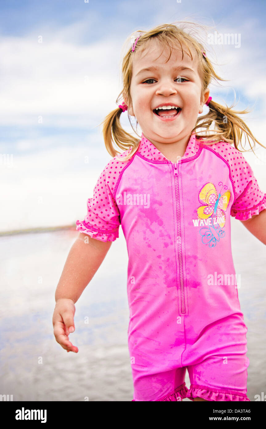 8d536b1307 Little girl running on the beach laughing - blond two year old toddler girl  in pink