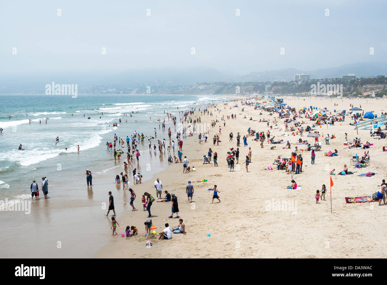 People enjoy the warm summer weather at Santa Monica beach in west Los Angeles, California. - Stock Image