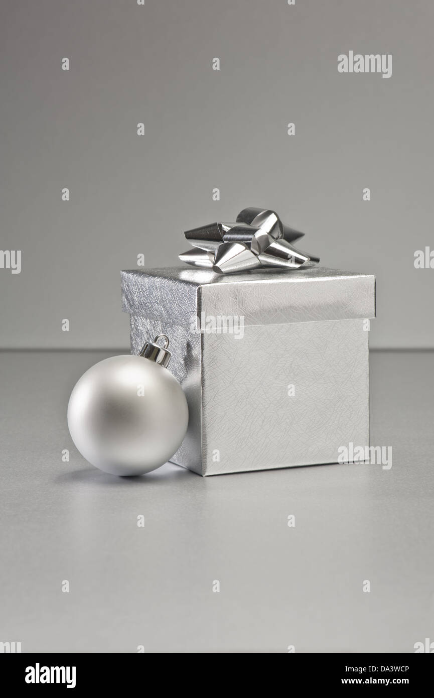 Silver bauble and present in Christmas setting Stock Photo