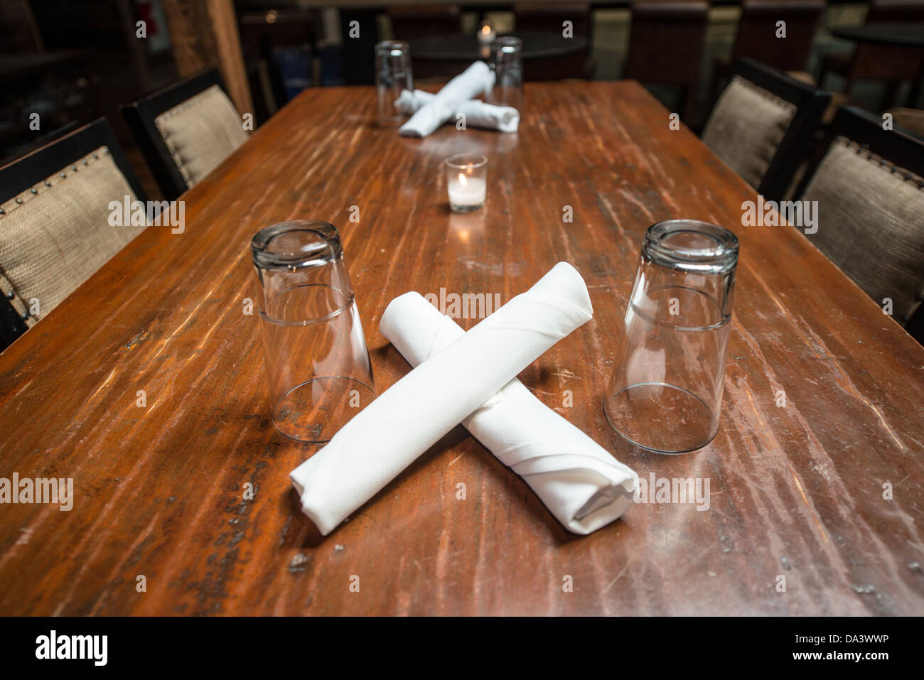 A simple table setting in a restaurant with a wooden table and the silverware wrapped & Simple Table Setting In Restaurant Stock Photos \u0026 Simple Table ...