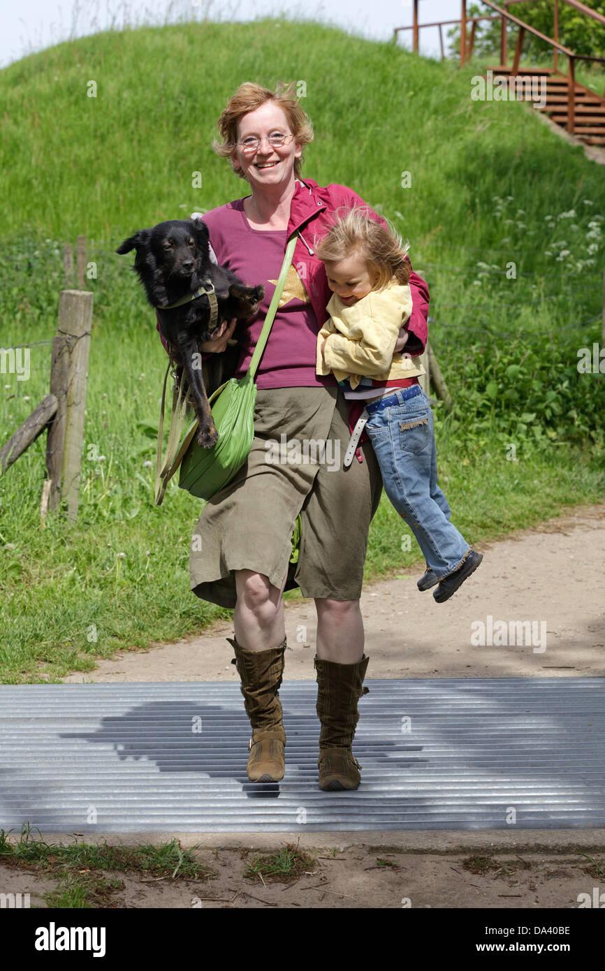a woman carrying dog and child, Haithabu, Schleswig-Holstein, Germany - Stock Image