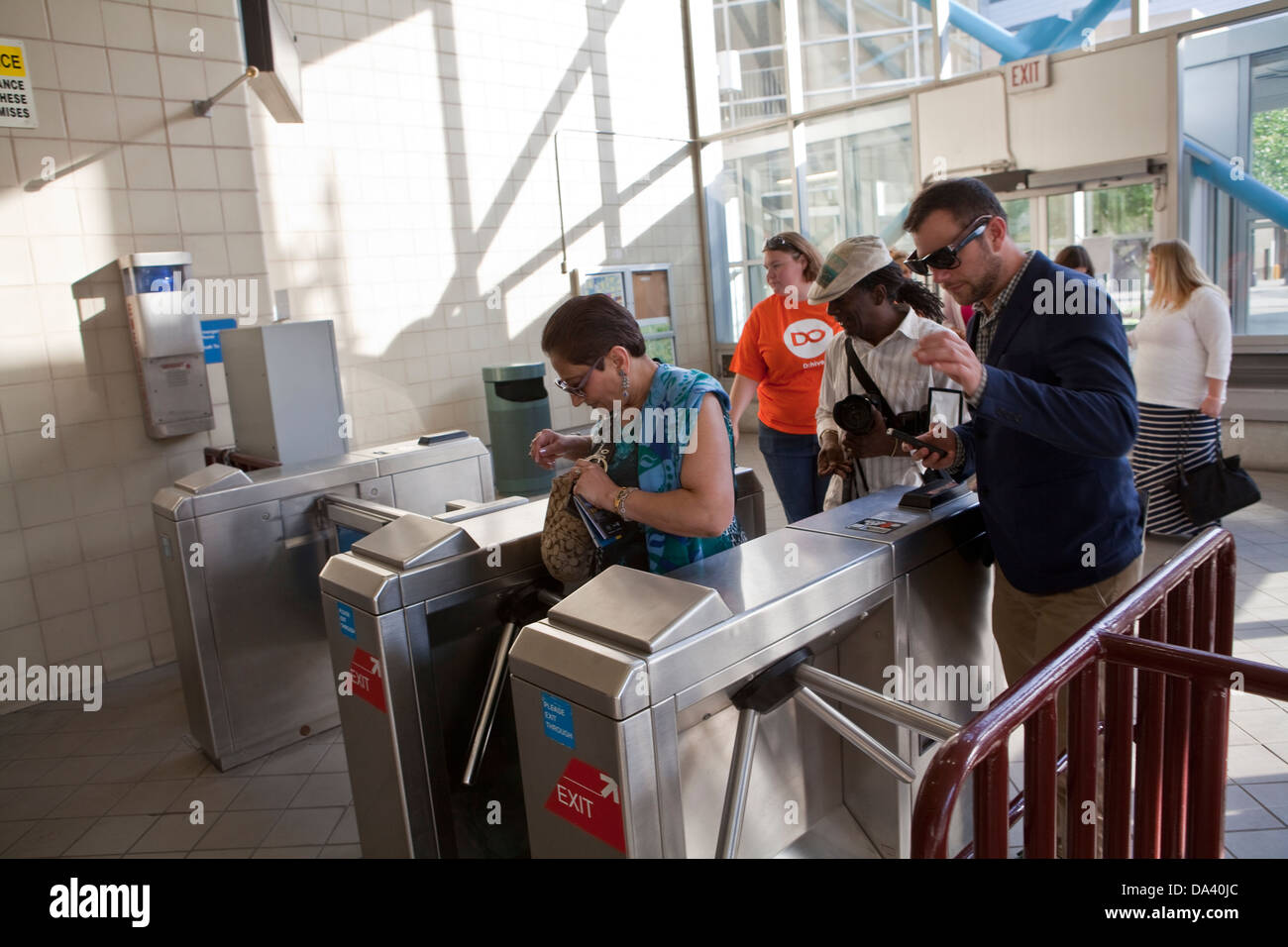 Commuters pay the fare at the turnstile of a The People Mover station in Detroit (Mi) - Stock Image