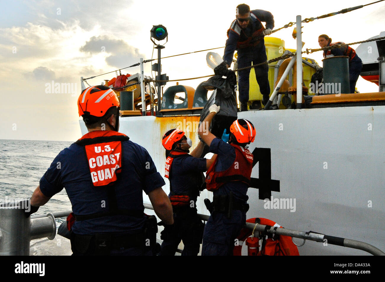 Crew members aboard the Coast Guard Cutter Northland transfers bales of contraband to a Coast Guard Station Miami Stock Photo