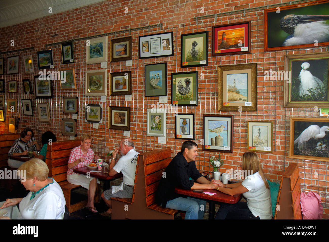 Brooksville Florida Rising Sun Cafe restaurant interior inside tables art paintings sale man woman couple - Stock Image