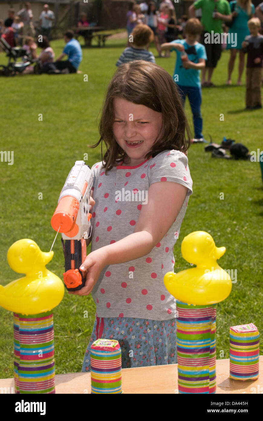 7 year old girl at summer fete using water pistol to squirt plastic ducks, Sheet, Hampshire, UK. - Stock Image