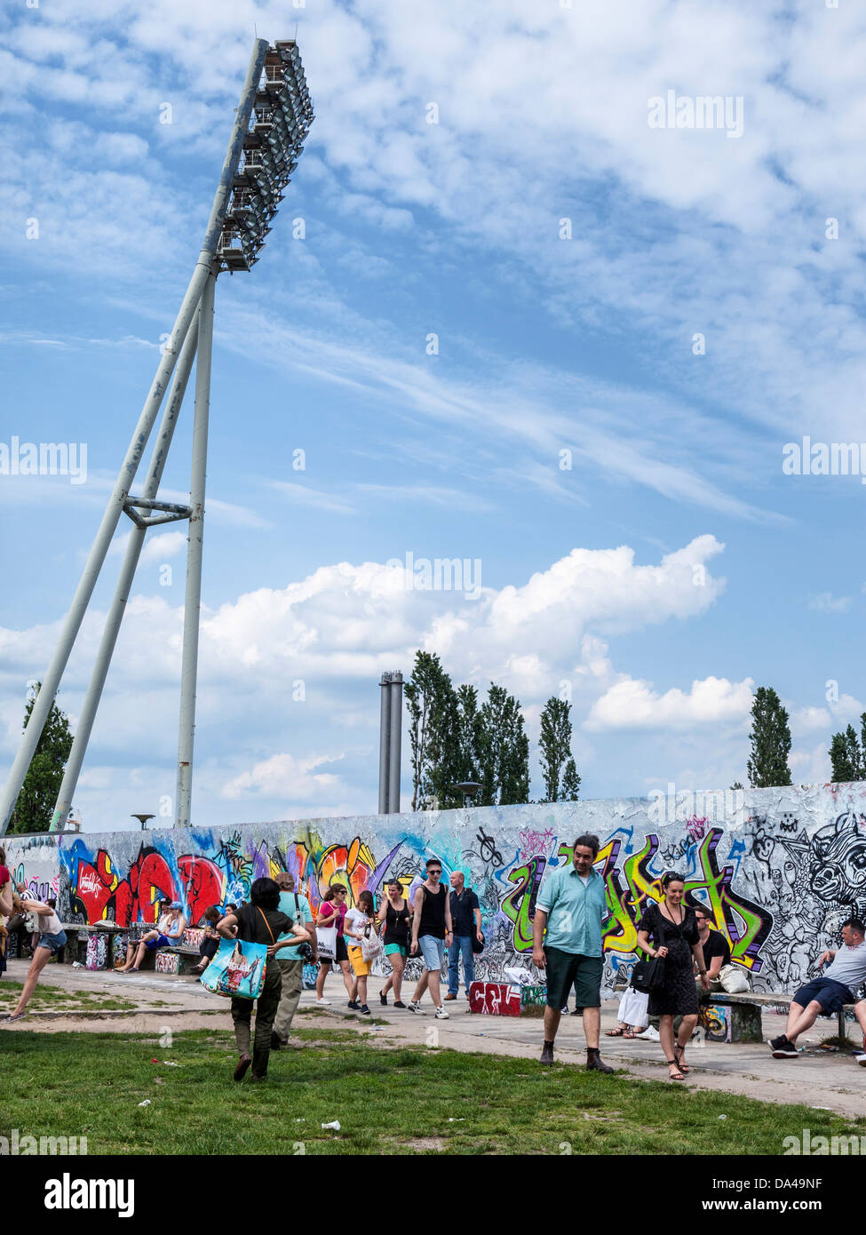 Graffiti covered Berlin wall and floodlight mast of the Friedrich Ludwig Jahn Sportpark - Mauer Park, Berlin - Stock Image