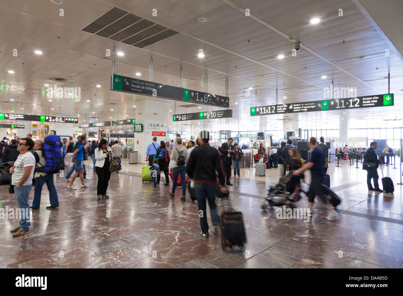 Passengers in the ticket hall at Barcelona Sants Railway Station. - Stock Image