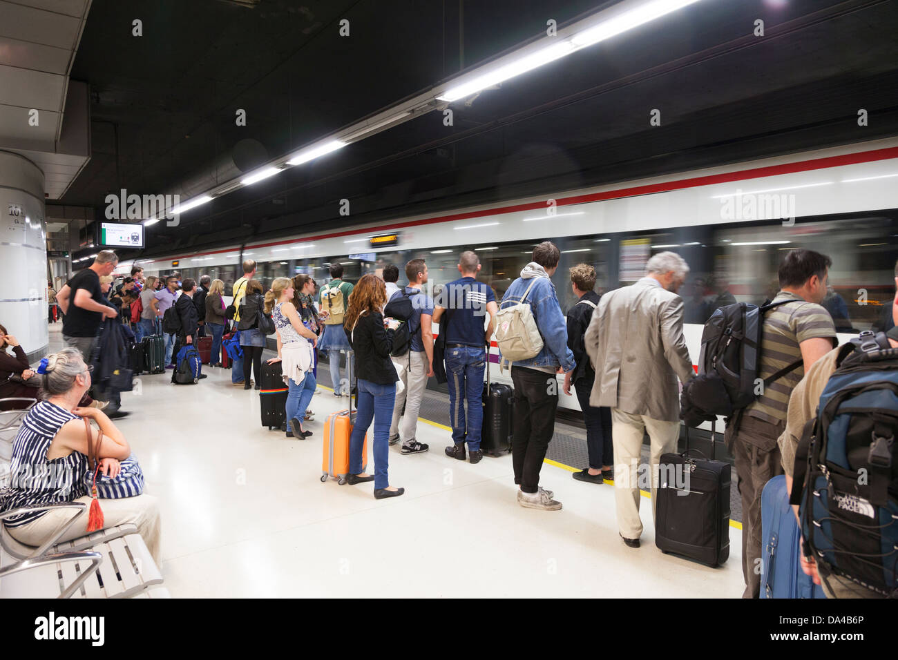 Passengers waiting on railway platform to board arriving train. - Stock Image