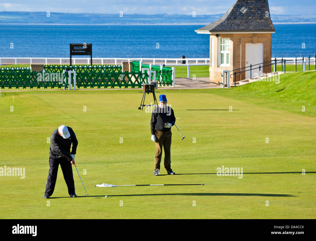 Two golfers putting at The Royal and Ancient Golf Club of St Andrews golf course St Andrews Fife Scotland UK GB - Stock Image
