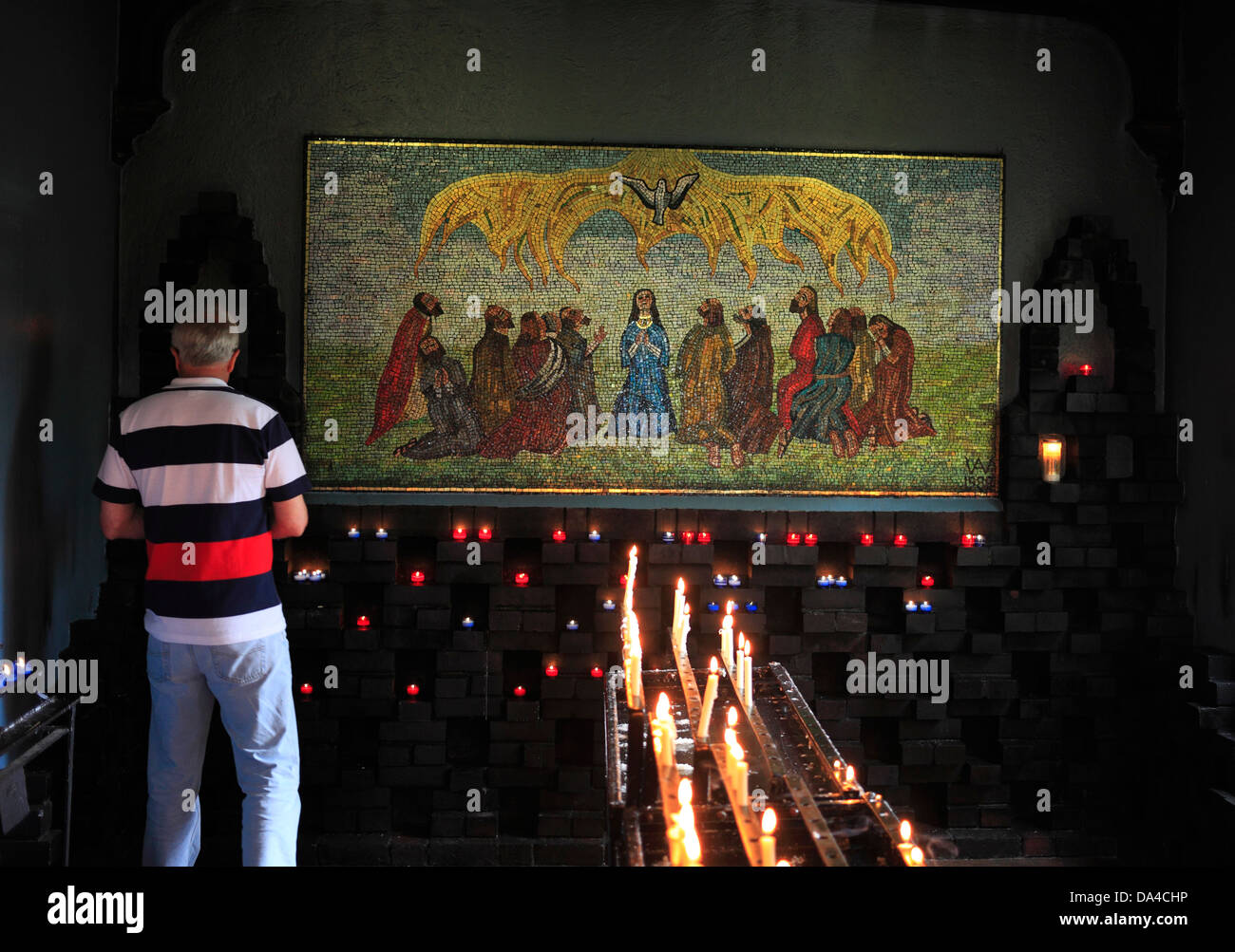 A man in front of the mosaic in the Chapel of the Holy Spirit, by Jewish artist Anna Wyner showing the event of - Stock Image