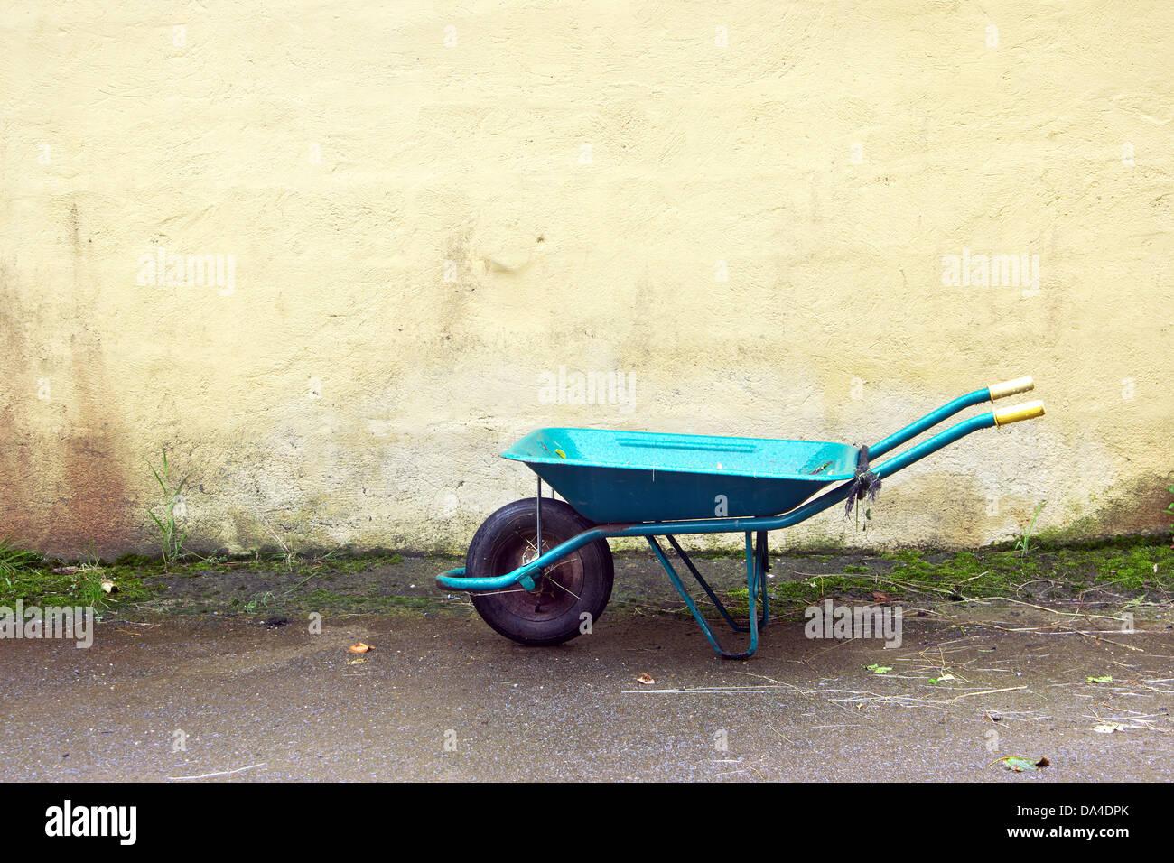 gardening wheelbarrow on a wall - Stock Image