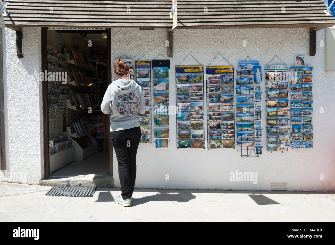 Young woman buying postcards from the Porthcothan Bay Stores Cornwall UK - Stock Image